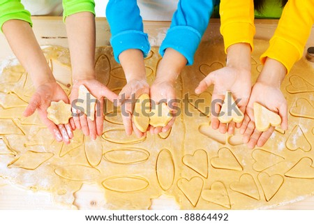 child's hands with dough over the table, top view - stock photo