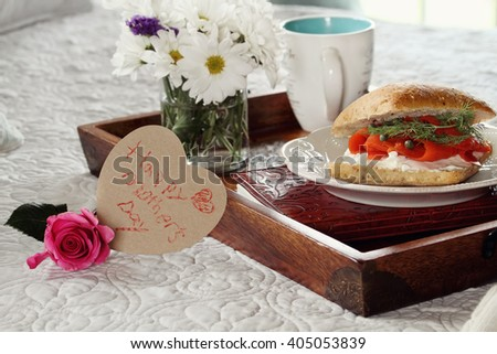 Child's handwriten message on heart shaped card and flowers with breakfast served in bed. Extreme shallow depth of field with selective focus on heart. - stock photo