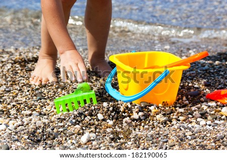 Child's legs and toys on the beach, family vacation  - stock photo