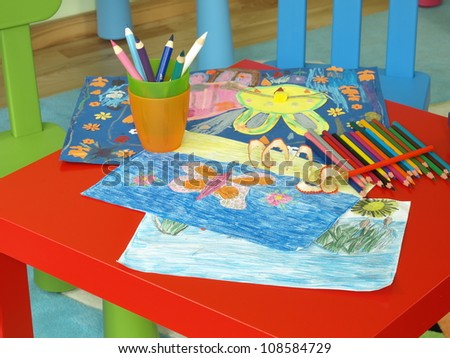 Child's paintings and colorful crayons on red table - stock photo