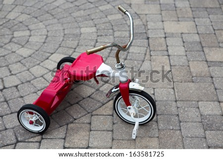 Child's red tricycle parked on a cobble design paved street - stock photo