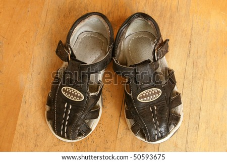 Child's sandals on a wooden background - stock photo