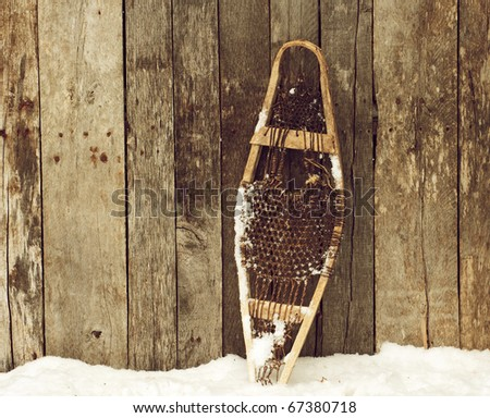 Child's snow shoe standing outside in the snow against a rustic wooden barn wall  with copy space. - stock photo