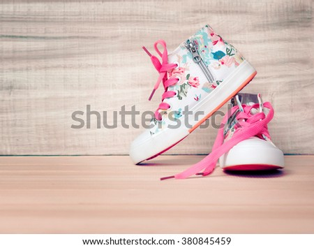 Child's textile sneakers white lace shoes on wooden floor background empty space.Childhood concept wallpaper.Kid's apparel. - stock photo