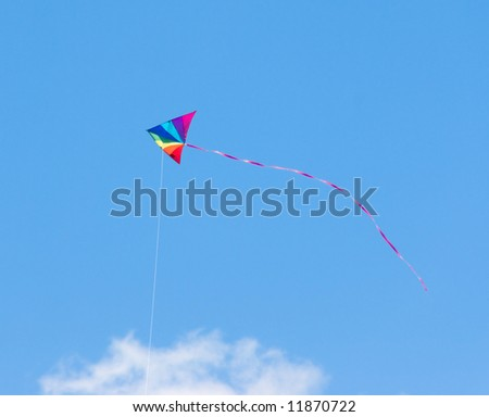 Child's toy kite in rainbow colors flying in a clear blue summer sky