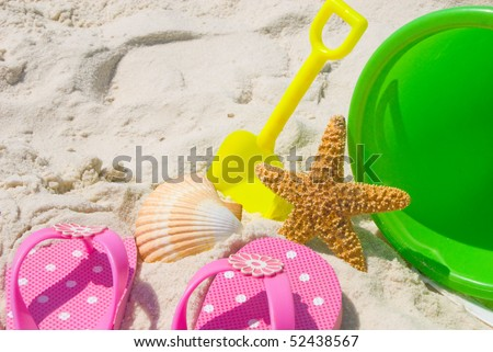 Child sandals and toys at beach - stock photo