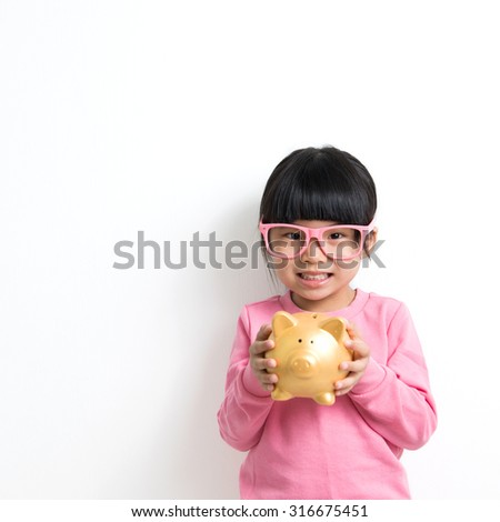Child savings, investment or money concept illustrated with Asian kid holding a piggy bank