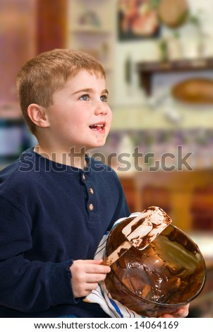Child scraping and eating batter from bowl - stock photo