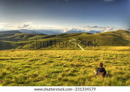 Child seated in a field looks towards mountains in the distance. Lessinia in Northern Italy.  - stock photo