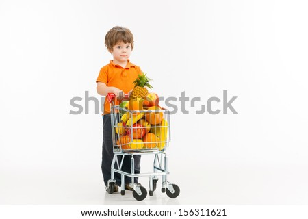 Child shopping. Cheerful little boy carrying shopping cart full of goods and looking at camera while isolated on white - stock photo