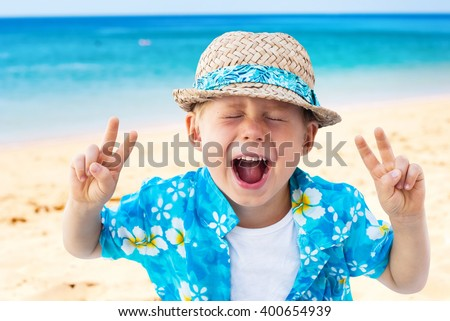 Child Shouts Laughs Hawaiian Shirt Straw Hat Holidays Clothes Isolated Natural Beach Sea Background - stock photo