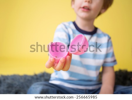 Child showing an open plastic easter egg, easter egg hunt concept.
