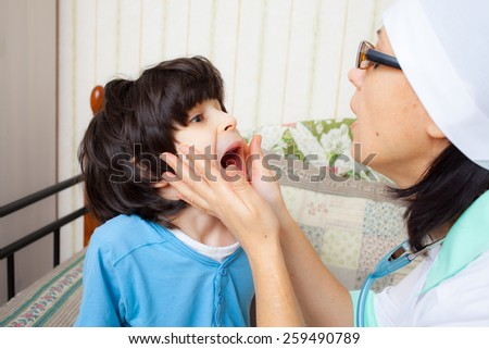 child showing his throat to doctor pediatrician - stock photo