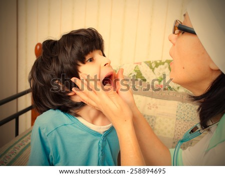 child showing his throat to doctor pediatrician. instagram image retro style - stock photo