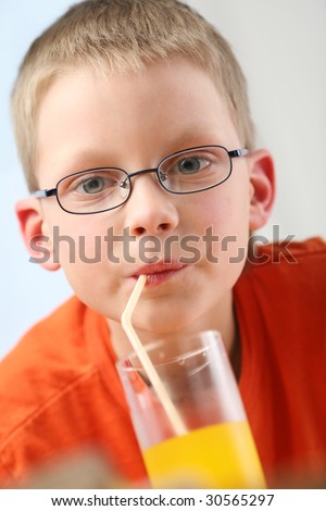 child sipping orange juice through straw - stock photo
