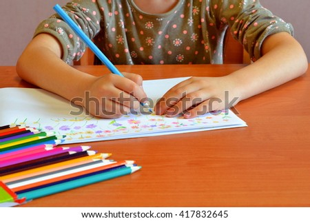 Child sits and draws flowers. Child holds a pencil in his hand. A set of colored pencils on a table. Kids drawing  - stock photo