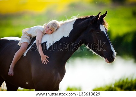 Child sits on a horse in meadow near small river. - stock photo
