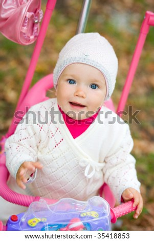 Child sits on a tricycle. - stock photo