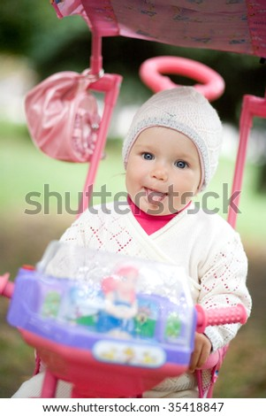 Child sits on a tricycle. She puts out the tongue. - stock photo