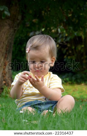 Child sits on the grass and play - stock photo