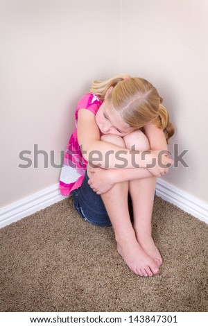 child sitting alone in corner with a sad look on face - stock photo