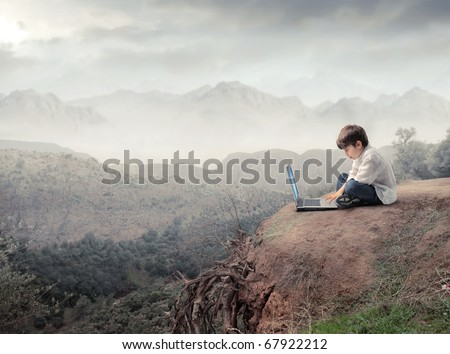 Child sitting and using a laptop with landscape on the background - stock photo