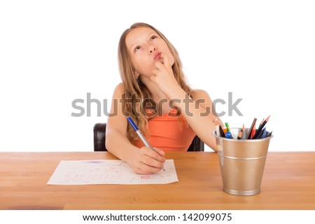 Child sitting at a wooden table trying to make a drawing. Isolated on a white background. - stock photo