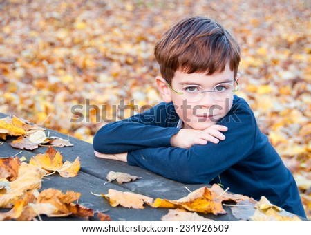Child sitting in autumnal park with his arms crossed - stock photo