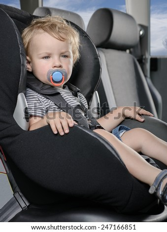Child sitting in car safety seat - stock photo