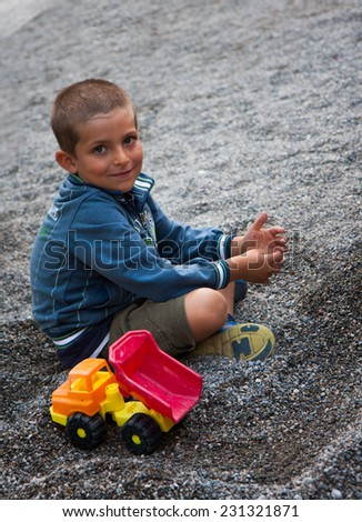 child sitting in the gravel with toy truck - stock photo