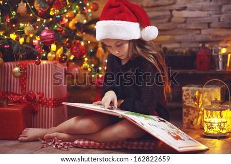 Child sitting near Christmas tree at night at home - stock photo