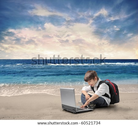 Child sitting on a beach and using a laptop