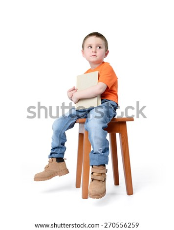 Child sitting on a chair with a book, on white background - stock photo