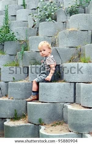 Child sitting on a concrete blocks - stock photo
