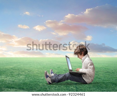 Child sitting on a green meadow and using a laptop - stock photo