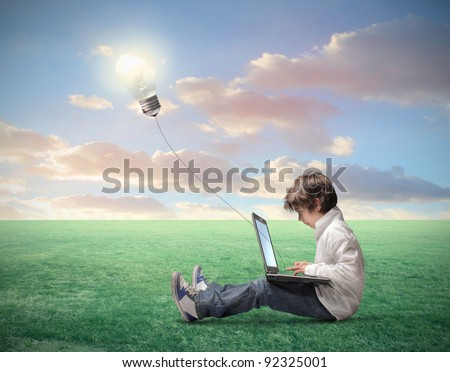 Child sitting on a green meadow and using a laptop with light bulb plugged in it - stock photo
