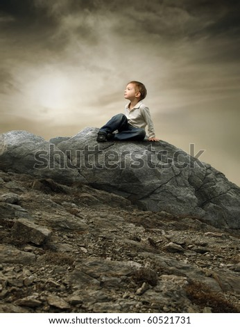 Child sitting on a rock - stock photo