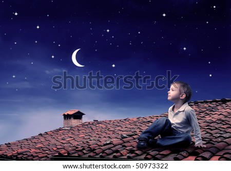 Child sitting on a rooftop and looking at the moon - stock photo