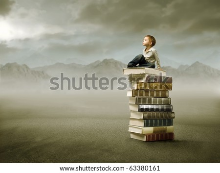 Child sitting on a stack of books in a desert - stock photo