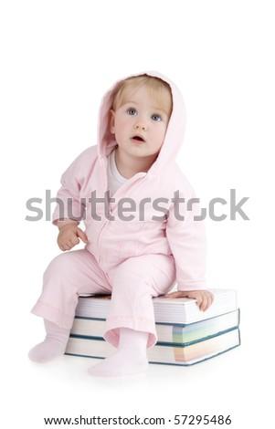 Child sitting on books on white background. - stock photo