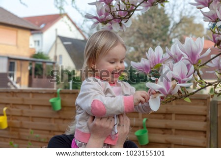 child sitting on mothers shoulder and picking some leaves of an magnolia tree