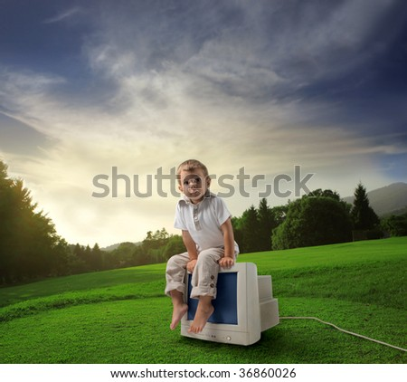 Child sitting on old computer in the countryside - stock photo