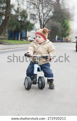 child sitting on runbike, little boy riding runbike - stock photo