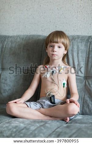 Child sitting on the sofa. Heart cardiogram or monitoring of cardiac performance using Holter. - stock photo