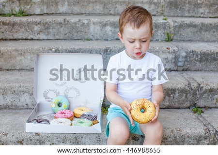 child sitting on the steps with a box of donuts. little boy playing with a donut. concept of junk food for kids - stock photo