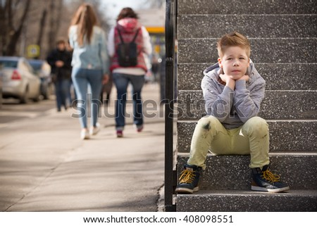 Child sitting on the stone steps. Portrait of handsome kid boy wearing casual sitting on the stairs on the street. Stylish boy looking at camera. Teenage boy, child outdoors in summer or spring. - stock photo