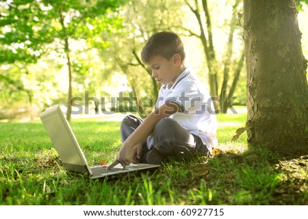 Child sitting under a tree in a garden and using a laptop - stock photo