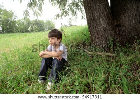 Child sitting under a tree on a green meadow - stock photo