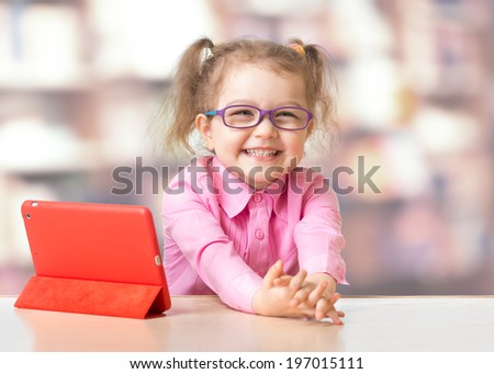 Child sitting with tablet computer in room