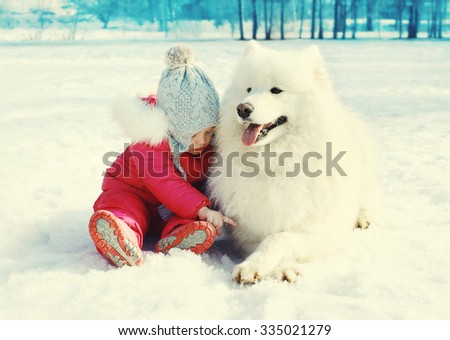 Child sitting with white Samoyed dog on snow in winter day - stock photo